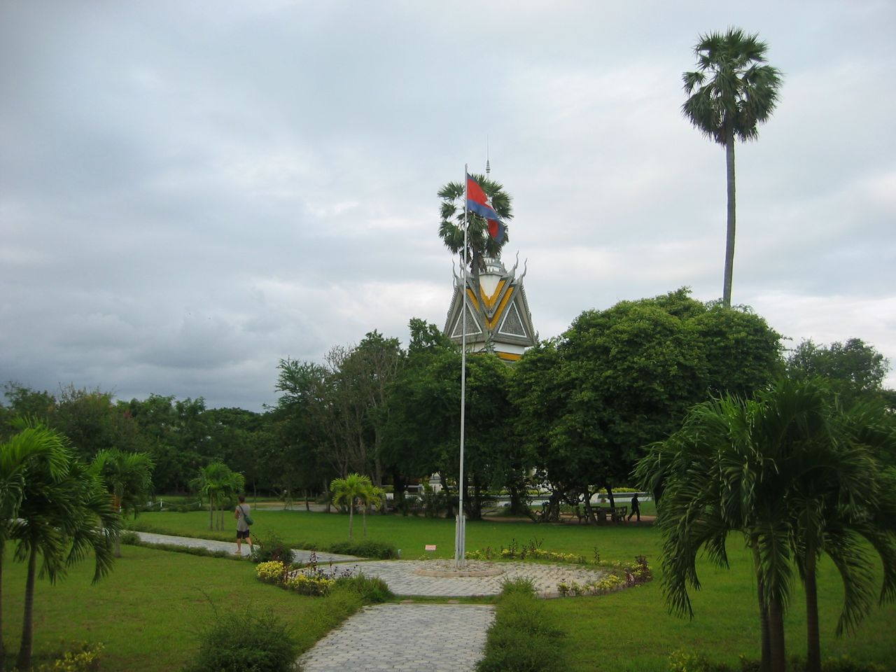 The Cambodian flag flies in front of a tree blocking the central monument structure.